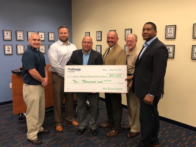 Fourth from Left to Right: Laura's Stand Down President, Larry Moore, and Laura's Stand Down Treasurer, Dean Wayne Wright with representatives of First Energy. — at Summit County Veterans Service Commission.
